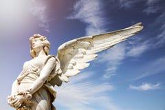Белая скульптура мрамора ангела с открытыми длинными крылами через рамку и против яркого солнечного голубого неба с пирофакелом о Стоковые Фото