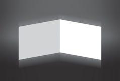 Белая сложенная бумага стоя на серой предпосылке Стоковые Фото