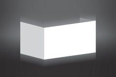 Белая сложенная бумага стоя на серой предпосылке Стоковое Изображение