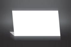 Белая сложенная бумага стоя на серой предпосылке Стоковое фото RF