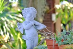 Белая статуя ангела купидона играя скрипку стоковое фото rf