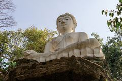 Белая статуя Будды на камне в виске Таиланда стоковые изображения