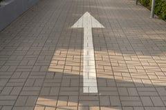 Белая стрелка на дороге вымощая плит, показывая направление стоковые фотографии rf