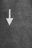 Белая стрелка на темноте - серый асфальт. Стоковая Фотография RF