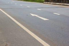 Белая стрелка указывая вперед на дорогу в Таиланде Стрелка на дороге асфальта Стоковые Фотографии RF