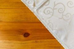 Белая ткань таблицы лежа на деревянном столе стоковая фотография