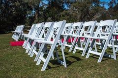 Белая церемония предводительствует установку outdoors с междурядьем красного ковра на зеленой траве Стоковое фото RF