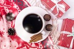 Белая чашка горячего кофе на белом белом рождества предпосылки шерстяном и красном подарке красного цвета завтрака утра рождества стоковые изображения rf