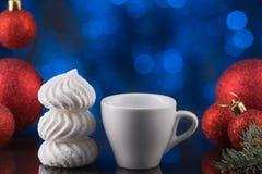 Белая чашка кофе в праздничном украшении, рождестве забавляется, голубая предпосылка bokeh, сладостный десерт Стоковые Изображения RF