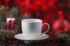 Белая чашка кофе в праздничном украшении, рождестве забавляется, красная предпосылка bokeh Стоковое фото RF