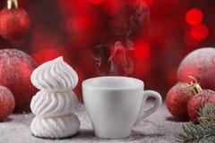 Белая чашка кофе в праздничном украшении, рождестве забавляется, красная предпосылка bokeh, сладостный десерт Стоковая Фотография