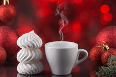 Белая чашка кофе в праздничном украшении, рождестве забавляется, красная предпосылка bokeh, сладостный десерт Стоковые Фото