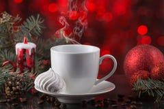 Белая чашка кофе в праздничном украшении, рождестве забавляется, красная предпосылка bokeh, сладостный десерт Стоковое фото RF