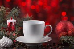 Белая чашка кофе в праздничном украшении, рождестве забавляется, красная предпосылка bokeh, сладостный десерт Стоковая Фотография RF
