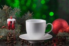 Белая чашка кофе в праздничном украшении, рождестве забавляется, зеленая предпосылка bokeh Стоковая Фотография