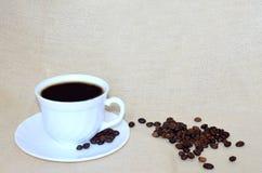 Белая чашка кофе, кофейные зерна на поддоннике и разбросанные рядом с ним Стоковые Изображения RF