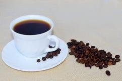 Белая чашка кофе, кофейные зерна на поддоннике и разбросанные рядом с ним Стоковые Изображения