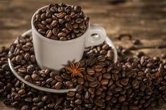 Белая чашка покрыла кофейные зерна с анисовкой звезды Стоковые Изображения RF