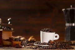 Белая чашка покрыла кофейные зерна с различными аксессуарами Стоковое Фото