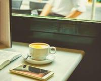 Белая чашка с капучино на таблице с открытым Smartphone книги на таблице кафа окном Атмосфера деревянного стула уютная Стоковое Фото