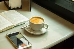 Белая чашка с капучино на таблице с открытым Smartphone книги на таблице кафа окном Стоковые Фото