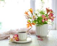 Белая чашка с чаем на таблице Цветки рядом Стоковое фото RF