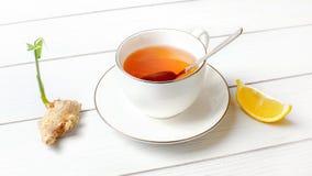 Белая чашка фарфора с горячим янтарным чаем, серебряная ложка в ей, сухой росток зеленого цвета корня имбиря и часть лимона на ст стоковые изображения rf