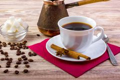 Белая чашка черного горячего кофе на поддоннике, который служат с кофейными зернами, кубами белого сахара в шаре, ложкой чая, ани Стоковое Фото