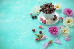 Белая чашка ягод сладостной вишни с розами и цветками на зеленой изумрудной предпосылке зрелые вишни и одичалые розы Стоковое фото RF
