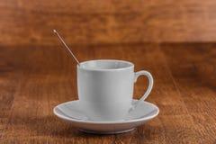 Белая чашка coffe с ложкой на белом поддоннике на предпосылке темного коричневого цвета деревянной Стоковое фото RF