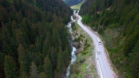 Белая шина едет дорогой в горной области к лыжному курорту Вид с воздуха белой шины в горах в Австрии видеоматериал