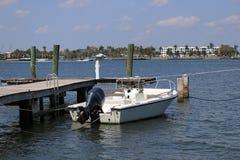 Белая шлюпка около частной пристани в Флориде в голубом море с голубым небом стоковые фото