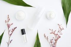 Белая cream помещенная бутылка, пустой пакет ярлыка для насмешки вверх на зеленой предпосылке листвы Стоковая Фотография RF