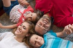 белизна взгляда мати фронта пола отца семьи дочи камеры backgroung счастливая целуя смотря лежа Стоковое фото RF