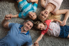 белизна взгляда мати фронта пола отца семьи дочи камеры backgroung счастливая целуя смотря лежа Стоковое Изображение