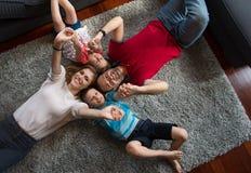белизна взгляда мати фронта пола отца семьи дочи камеры backgroung счастливая целуя смотря лежа Стоковая Фотография