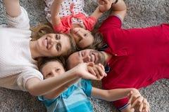 белизна взгляда мати фронта пола отца семьи дочи камеры backgroung счастливая целуя смотря лежа Стоковые Фото