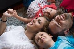 белизна взгляда мати фронта пола отца семьи дочи камеры backgroung счастливая целуя смотря лежа Стоковые Изображения