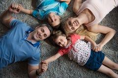белизна взгляда мати фронта пола отца семьи дочи камеры backgroung счастливая целуя смотря лежа Стоковая Фотография RF