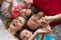 белизна взгляда мати фронта пола отца семьи дочи камеры backgroung счастливая целуя смотря лежа Стоковые Изображения RF