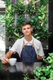 Белизна кельнера зеленая выходит портрету кофейной чашки молодой мужской день St. Patrick рисбермы кафа клиента кофе обслуживания стоковая фотография
