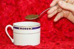белизна кофейной чашки предпосылки красная Владение руки ложка Стоковые Изображения