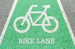 Белизна крупного плана покрашенная велосипеда подписывает внутри зеленую майну велосипеда на поле улицы в предпосылке текстуриров Стоковая Фотография