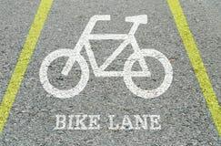 Белизна крупного плана покрашенная велосипеда подписывает внутри майну велосипеда на поле улицы в предпосылке текстурированной па Стоковое Изображение