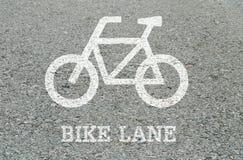 Белизна крупного плана покрашенная велосипеда подписывает внутри майну велосипеда на поле улицы в предпосылке текстурированной па Стоковая Фотография