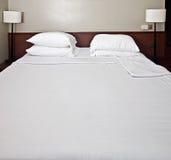 белизна спальни постельных принадлежностей роскошная Стоковые Изображения