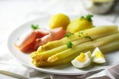 Белое блюдо спаржи с картошками, ветчиной и яичком на белой плите Стоковая Фотография RF