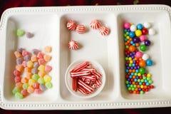Белое блюдо с сортированной красочной конфетой праздника стоковое изображение