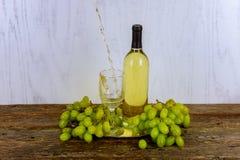 Белое вино и виноградины Wine и виноградины на винтажном деревянном столе Стоковое фото RF