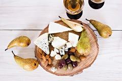 Белое вино и закуски Вино, виноградины, сыр, гайки, оливки Романтичный вечер, натюрморт Стоковое Фото